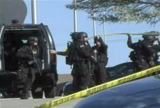 <p>Команда полицейского спецназа оцепляет американскоую военную базу Форт Худ 5 ноября 2009 года. Жертвами стрельбы, устроенной врачом-психиатром на американской военной базе Форт Худ, стали 12 человек, еще 31 один был ранен, сообщили представители армии. REUTERS/Department of Defense Video/Handout</p>