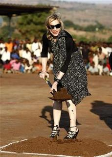 U.S. singer Madonna turns the soil to lay the foundation of a multi-million dollar girls' school she is building in Chinkota, outside Lilongewe in Malawi October 26, 2009. REUTERS/Siphiwe Sibeko