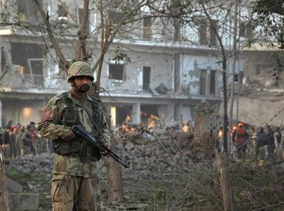 A soldier stands guard at the site of a suicide bomb blast in Peshawar November 13, 2009. REUTERS/K Parvez