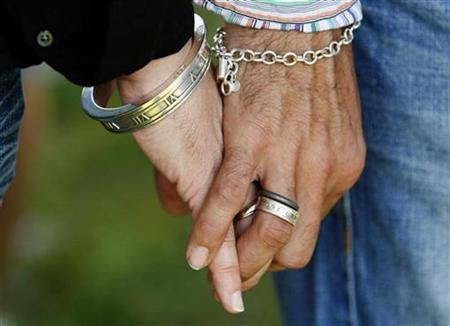 Gay couple Fernando Christopher, 40, (L) and his spouse Michael Domino Christopher, 35, hold hands as they celebrate their one-year wedding anniversary in West Hollywood, California, June 16, 2009. REUTERS/Lucy Nicholson
