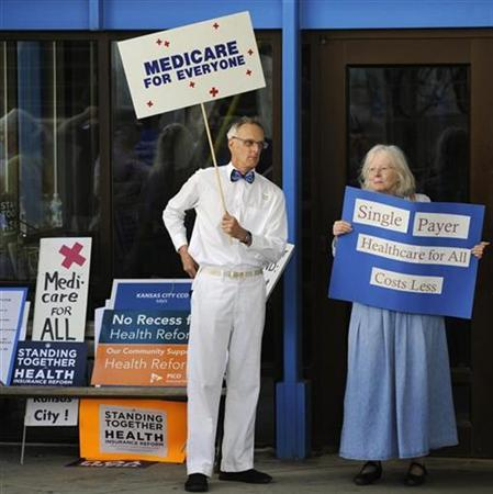 Healthcare reform supporters display their signs by a stack of others that were not allowed into a healthcare forum at the UMKC campus in Kansas City, Missouri, August 24, 2009. REUTERS/Dave Kaup