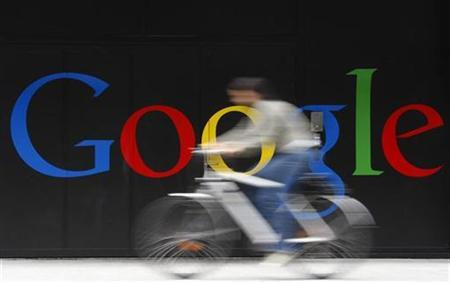 An employee rides her bike past a logo next to the main entrance of the Google building in Zurich in this July 9, 2009 file photo. REUTERS/Christian Hartmann