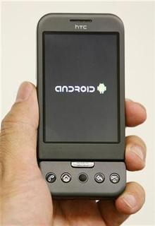 A Singapore Telecommunications representative displays the HTC Dream phone, which runs Google Inc's Android operating system, during a preview for Reuters in Singapore February 20, 2009. REUTERS/Vivek Prakash