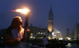 <p>In questa immagine di archivio l'atleta Manuela Levorato porta la torcia olimpica su una gondola a Venezia passando davanti a piazza San Marco. REUTERS/Tony Gentile</p>