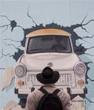 """<p>Мужчина рассматривает восточногерманский автомобиль """"Трабант"""", нарисованный на отреставрированном сегменте Берлинской стены 8 ноября 2009 года. Их булькающие двигатели, зубодробительные подвески и архаичный дизайн когда-то покорили улицы всех городов за """"железным занавесом"""", а теперь автомобиль """"Трабант"""" и его родственники - лакомый кусочек для коллекционеров. REUTERS/Thomas Peter</p>"""