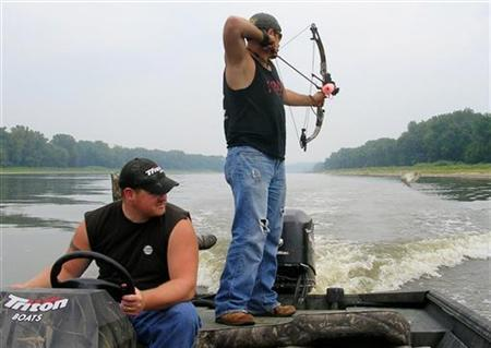 Chris Brackett (R) and Troy Green bow hunt for jumping Asian carp on the Illinois River in Peoria, Illinois August 25, 2006. The carp are easily spooked and jump out of the water when they sense outboard motors. REUTERS/James Kelleher