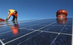 <p>Un operaio monta pannelli solari sul tetto di un edificio. REUTERS/Tim Wimborne</p>
