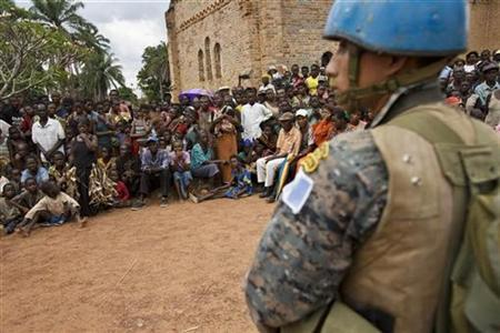 A U.N. soldier stands guard as residents gather for a visit by U.N. humanitarian chief John Holmes in Dorouma, Congo, near the border with Sudan, February 9, 2009. REUTERS/T.J. Kirkpatrick/Pool