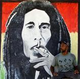 """<p>Мужчина стоит у портрета звезды регги Боба Марли в Кингстоне, Ямайка 12 июля 2001 года. Американская Академия звукозаписи в очередной раз дополнила свой """"Зал славы Грэмми"""", на этот раз песнями Джеймса Брауна, Боба Марли, Beach Boys, Луи Армстронга и других, доведя общее число удостоившихся такой чести треков до 851. REUTERS/Kimberly White</p>"""