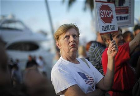 A resident of south Florida holds a sign protesting healthcare reforms during a visit by President Barack Obama to Miami, Florida, October 26, 2009.REUTERS/Carlos Barria