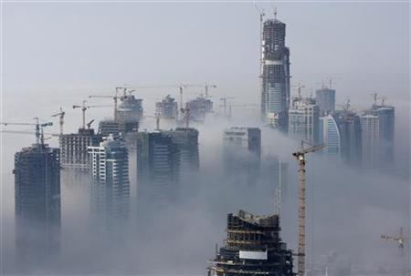 Fog rolls by early in the morning, as construction cranes work, near the Dubai Marina construction and residential zone, in Dubai September 20, 2007. REUTERS/Steve Crisp