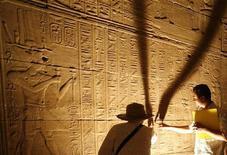 <p>Турист и экскурсовод рассматривают иероглифы на стене храма в Асуане, Египет 26 апреля 2009 года. Путешествия опять становятся популярны, несмотря на охвативший мир финансовый кризис, так как каждый пятый человек планирует в скором времени отдохнуть за рубежом, говорится в международном исследовании компании MasterCard. REUTERS/Asmaa Waguih</p>