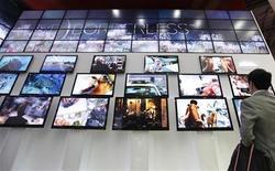 <p>Un'immagine di archivio di un uomo che osserva alcuni monitor tv. REUTERS/Lee Jae-Won</p>