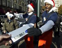 """<p>Rappresentanti di shopping.com, sito di shopping site, consegnano banconote da un dollaro a New York durante il """"Black Friday"""". REUTERS/Ray Stubblebine/shopping.com/Handout</p>"""