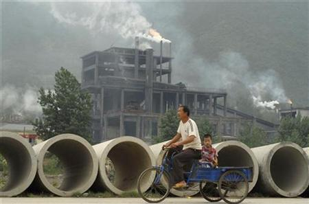 A man rides a tricycle with his son past a cement plant in Baokang, Hubei province, July 13, 2009. REUTERS/Stringer