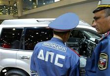 <p>Сотрудники ГИБДД рассматривают автомобиль на автошоу в Москве 30 августа 2006 года. Российская госавтоинспекция хочет выявлять нарушения, наказывать водителей и собирать штрафы с помощью автоматизированной системы в надежде увеличить поступления в казну. REUTERS/Anton Denisov</p>