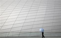 <p>A police officer walks with an umbrella outside the brand new National Academy for the Performing Arts building in Port-of-Spain November 24, 2009. REUTERS/Jorge Silva</p>