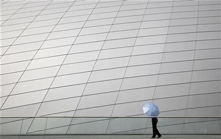 A police officer walks with an umbrella outside the brand new National Academy for the Performing Arts building in Port-of-Spain November 24, 2009. REUTERS/Jorge Silva