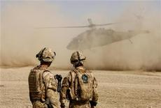 <p>Британские солдаты наблюдают за взлетом вертолета в провинции Гильменд в Афганистане 26 июля 2009 года. Европейские лидеры поспешили поддержать афганскую стратегию президента США Барака Обамы, но не торопятся давать обещания об участии своих войск в смертельно опасной военной кампании. REUTERS/Omar Sobhani</p>