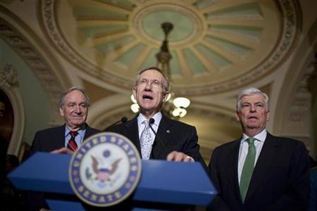 Senate Majority Leader Harry Reid (C)(D-NV) speaks as Tom Harkin (L)(D-IA) and Christopher Dodd (D-CT) listen after the U.S. Senate voted to begin debate on legislation for a broad healthcare overhaul on Capitol Hill in Washington November 21, 2009. REUTERS/Joshua Roberts
