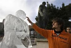 <p>Un volontario di Greenpeace di fronte alla scultura di ghiaccio che raffigura Silvio Berlusconi. REUTERS/Chris Helgren (ITALY ENVIRONMENT SOCIETY IMAGES OF THE DAY)</p>