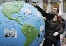 <p>Personas miran un enorme globo terráqueo en el centro de Copenhague, 7 dic 2009. La cumbre más grande de la historia sobre el clima comenzó el lunes con una descarnada advertencia de la ONU sobre el riesgo de la desertificación y el aumento del nivel de los mares, mientras los anfitriones daneses dijeron que es posible llegar a un acuerdo. Políticos y científicos instaron a que en los diálogos, que se desarrollan entre el 7 y el 18 de diciembre y a los cuales asisten 15.000 delegados de cerca de 190 naciones, se acuerden acciones inmediatas para limitar la emisión de gases invernadero, señalados como responsables del calentamiento global. REUTERS/Pawel Kopczynski</p>