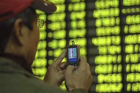 An investor takes photos in front of an electronic board with stock information at a brokerage house in Shanghai November 24, 2009. REUTERS/Stringer