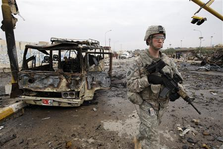 A U.S. soldier walks past a burned bus at the site of a bomb attack in northern Baghdad, December 8, 2009. REUTERS/Thaier al-Sudani