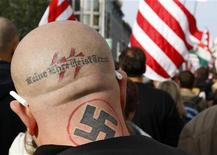 <p>Сторонник правых взглядов на демонстрации в Будапеште 23 октября 2009 года. Суд американского Санкт-Петербурга постановил замазать свастику и другие татуировки подсудимого неонациста Джона Дитуллио, чтобы рисунки не смущали присяжных. REUTERS/Laszlo Balogh</p>