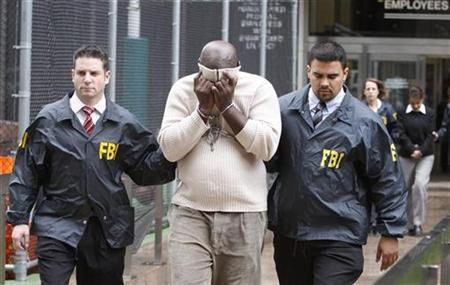 Emmanuel Roy, a suspect in a mortgage-fraud scheme is escorted by FBI agents after being taken into custody in New York, October 15, 2009. REUTERS/Brendan McDermid