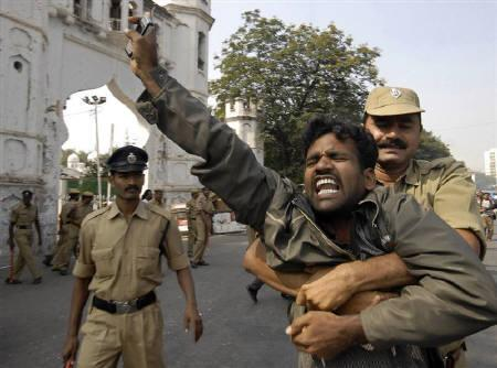 Policemen detain a protester in Hyderabad December 9, 2009. The government will carve a new state called Telangana out of Andhra Pradesh. REUTERS/Krishnendu Halder