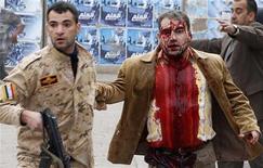 """<p>Иракский солдат помогает мужчине, пострадавшему при взрыве бомбы в Багдаде 8 декабря 2009 года. DИракские боевики, связанные с международной экстремистской сетью """"аль-Каида"""", взяли на себя ответственность за серию взрывов в Багдаде, в результате которой погибли 112 человек. REUTERS/Stringer</p>"""