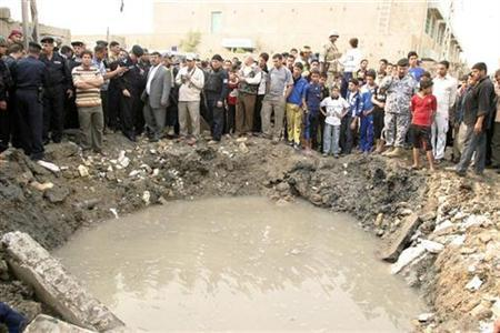 Residents and security personnel gather around a crater after a bomb attack in Baghdad's Sadr City, December 7, 2009. REUTERS/Stringer