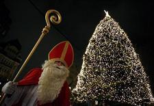 """<p>Мужчина, одетый как Святой Николай, у рождественской ели в Гамбурге 6 декабря 2008 года. В Германии девушка, заплакавшая после того, как полицейский выписал ей штраф за превышение скорости, получила рождественский """"подарок"""" - другая женщина, остановленная за такое же нарушение, заплатила штраф за нее. REUTERS/Christian Charisius</p>"""