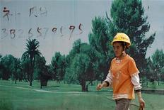 <p>Рабочий идет мимо постера, заслоняющего строительство новой станции метро в Шэньчжэне, китайская провинция Гуандун 9 ноября 2009 года. Спор двух китайских компаний о праве на производственную площадку закончился массовой дракой сотен рабочих, вооруженных взрывчаткой, камнями и стальными трубами, сообщили китайские государственные СМИ в пятницу. REUTERS/Tyrone Siu</p>