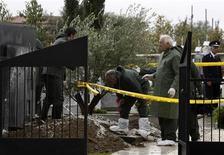 <p>Полицейские стоят рядом с оскверненной могилой бывшего президента Кипра Тассоса Пападопулоса 11 декабря 2009 года. Вандалы разрыли могилу бывшего президента Кипра Тассоса Пападопулоса и похитили его тело, сообщил в пятницу источник в правоохранительных органах страны. REUTERS/Andreas Manolis</p>