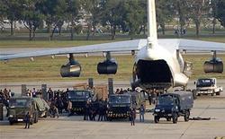 <p>Сотрудники служб безопасности окружают самолет, совершивший вынужденную посадку в аэропорту Бангкока 12 декабря 2009 года. Власти Таиланда расследуют инцидент с поставками оружия из Северной Кореи на борту задержанного в минувшие выходные в аэропорту Бангкока самолета Ил-76 с экипажем из стран СНГ. REUTERS/Stringer</p>