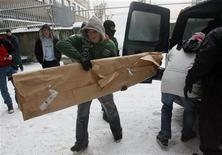 """<p>Мужчина выносит из фургона завернутый в бумагу фрагмент вывески """"Arbeit macht frei"""" в Кракове 21 декабря 2009 года. Пятеро мужчин, задержанных за похищение вывески, висевшей над входом в бывший немецкий концлагерь Аушвиц (Освенцим), преследовали корыстные цели и не являются членами неонацистских группировок, сообщила в понедельник польская полиция. REUTERS/HO</p>"""