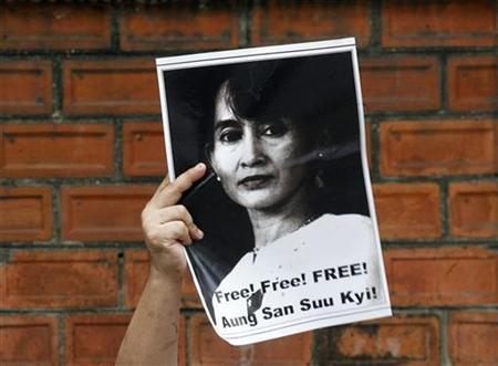 A Myanmar national living in Thailand holds a portrait of pro-democracy icon Aung San Suu Kyi during a rally calling for Suu Kyi's release, outside the Myanmar embassy in Bangkok August 11, 2009. REUTERS/Kerek Wongsa