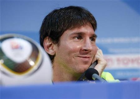 Barcelona's Lionel Messi smiles during a news conference at Zayed Sport City stadium in Abu Dhabi December 18, 2009.REUTERS/Fadi Al-Assaad