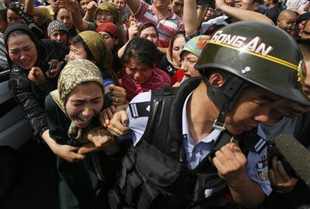 A woman holds onto a Chinese policeman as a crowd of locals confront security forces along a street in the city of Urumqi, in China's Xinjiang Autonomous Region July 7, 2009. REUTERS/David Gray