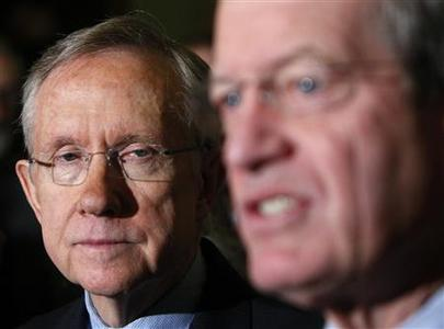 Senate Majority Leader Harry Reid (L) listens to Senator Max Baucus after the U.S. Senate approved President Barack Obama's healthcare overhaul on Capitol Hill in Washington, December 24, 2009. REUTERS/Jim Young