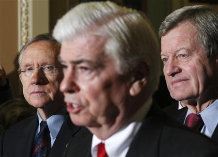 U.S. Senate Majority Leader Harry Reid (D-NV) (L) and Senator Max Baucus (D-MT) (R) listen to Senator Christopher Dodd (D-CT) after the U.S. Senate approved President Barack Obama's healthcare overhaul on Capitol Hill in Washington December 24, 2009. REUTERS/Jim Young