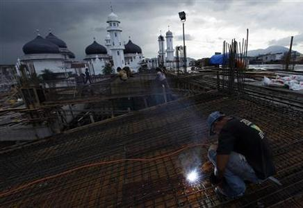 A worker welds a steel rod at a construction site near Baiturrahman mosque in Banda Aceh December 25, 2009. REUTERS/Beawiharta