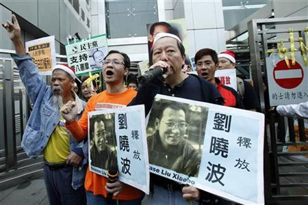 Protestors hold placards during a protest urging for Liu Xiaobo's release outside the Chinese liaison office in Hong Kong December 25, 2009. REUTERS/Tyrone Siu