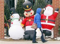 <p>Una donna passa davanti ad alcuni pupazzi natalizi mentre si reca a fare shopping. REUTERS/Brian Snyder</p>