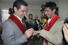 <p>Jose Maria Di Bello (L) and his partner Alex Freyre exchange rings as they get married at a government's registry office in Ushuaia, December 28, 2009. REUTERS/Tierra del Fuego government/Handout</p>
