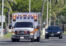 <p>Ambulância é escoltada por um carro na rua onde o presidente dos EUA, Barack Obama, passa férias com a família e amigos no Havaí REUTERS/Larry Downing</p>