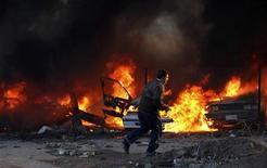 <p>Мужчина пытается убежать с места взрыва в центре Багдада 15 декабря 2009 года. Два смертника взорвали себя в центре города Эр-Рамади на западе Ирака в среду утром, убив по меньшей мере 20 и ранив более 100 человек, сообщила полиция. REUTERS/Stringer</p>