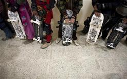 <p>Afghan children hold their skateboards as they wait in line to enter the skateboarding park in Kabul December 29, 2009. REUTERS/Marko Djurica</p>